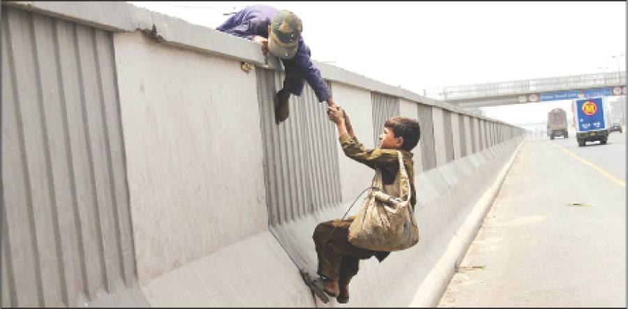 ایک خانہ بدوش بچہ رنگ روڈ کی دیوار پرچڑھنے کی کوشش کر رہا ہے، ایسی صورت حال کسی وقت بھی بڑے حادثہ کا سبب بن سکتی ہے