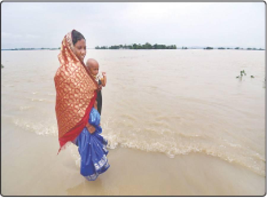 موریگوان، بھارتی ریاست آسام کے علاقے میں ایک خاتون اپنے بچے کو اٹھائے سیلابی پانی سے گزر رہی ہے