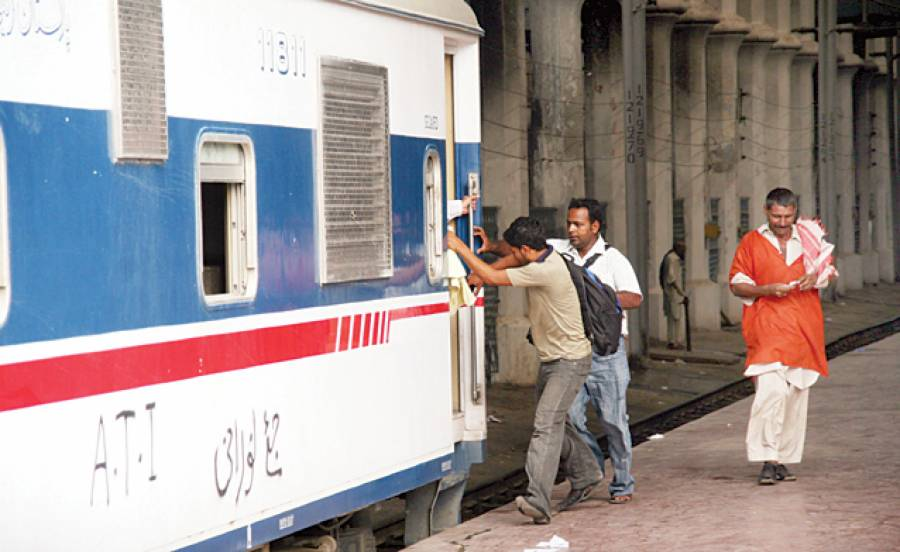 لاہور: دو نوجوان چلتی ٹرین پر سوار ہو رہے ہیں جبکہ قلی پیسے گن رہا ہے