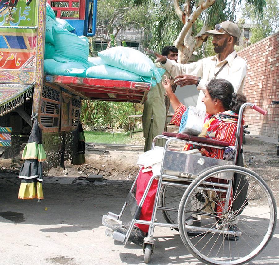 لاہور: سستا رمضان بازار میں معذور خاتون ٹرک سے آٹا خرید رہی ہے
