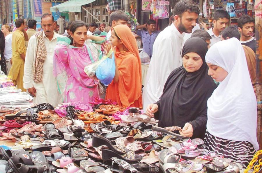 خواتین عید کی تیاریوں کے سلسلے میں ایک سٹال سے جوتیاں خرید رہی ہیں