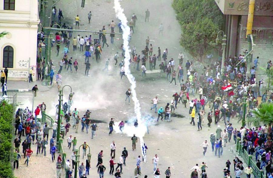 قاہرہ:مصری صدر محمد مرسی کے خلاف احتجاج کے دوران مظاہرین پولیس کی جانب سے پھینکی گئی آنسو گیس سے بچنے کے لئے بھاگ رہے ہیں