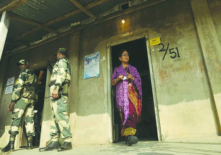 گامچا کوبرا: بھارتی پولیس اہلکار ایک پولنگ سٹیشن کے باہر تعینات ہیں جبکہ ایک خاتون اپنا ووٹ کاسٹ کرنے کے بعد باہر آرہی ہے