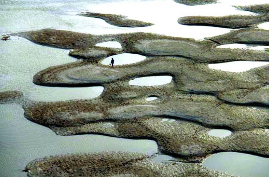 بیجنگ: چینی صوبے شیان میں ایک شخص خشک دریاکے درمیان میں واقع ٹیلوں پر سے گزررہاہے