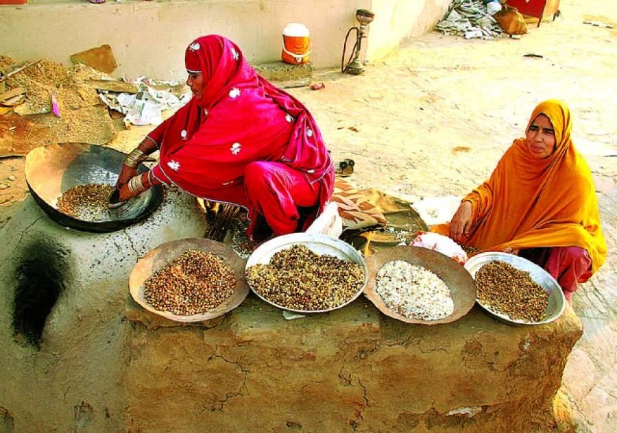 رزق حلال عین عبادت ہے محنت کش خواتین بھٹی پر دانے بھون رہی ہیں۔فوٹو پاکستان