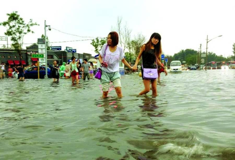 بیجنگ: خواتین شدید بارش کے باعث سڑک پر کھڑے پانی میں اپنے گھر جا رہی ہیں