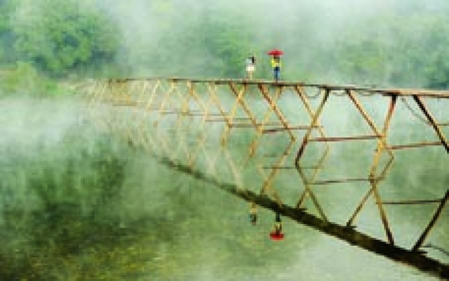 بیجنگ: دھند میں دو خواتین لکڑی کے پل پر سے گزر رہی ہیں