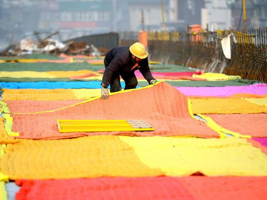 چین میں یہ مزدور سڑک کے اوپر رنگ برنگے کمبل کیوں بچھا رہا ہے؟ وجہ ایسی کہ آپ بھی چینیوں کو داد دیں گے