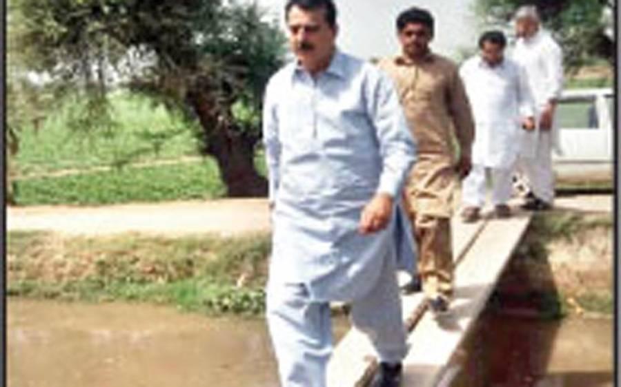 سابق وزیراعظم سید یوسف رضا چلتی نہر پر کھمبوں کا عارضی پل کراس کر کے ووٹ مانگنے گئے