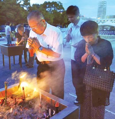 جاپان ' لوگ ہیرو شیما پر اٹیم بم کے حملہ میں ہلاک ہونےوالوں کی یاد میں منعقدہ تقریب کے دوران دعا کر رہے ہیں