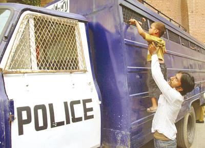 لاہور، بچہ قیدیوں کی گاڑی میں بند اپنے باپ سے ہاتھ ملا رہا ہے