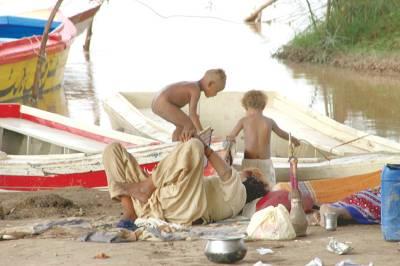 راوی کنارے خانہ بدوش فیملی کے بچے دریائی موجوں سے بے خبر کشتیوں میں کھیل رہے ہیں