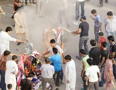 لاہور:توہین آمیز فلم کے خلاف احتجاج کے دوران مشتعل افراد امریکی اور اسرائیلی پرچم نذر آتش کر رہے ہیں