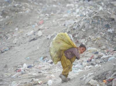 کابل: کوڑا کرکٹ جمع کرنے والا افغان بچہ کوڑے کا تھیلہ اٹھائے جا رہا ہے