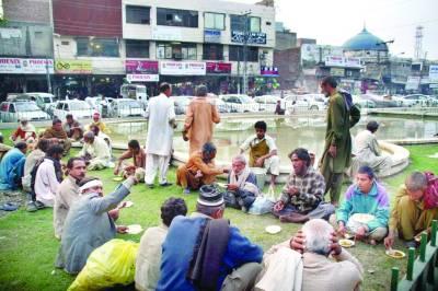 نیلا گنبد کے علاقے میں ایک ہوٹل والے کی طرف سے تقسیم کیا گیا کھانا غریب افراد زمین پر بیٹھ کر کھا رہے ہیں(فوٹو عمر شریف)