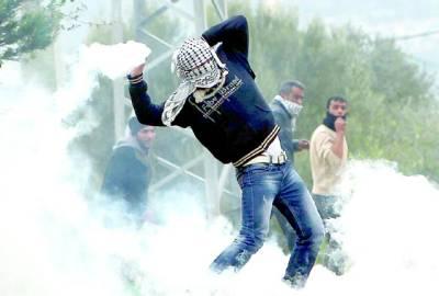 کفردوم : فلسطینی مظاہرین جھڑپوں کے دوران آنسو گیس کا گولہ واپس اسرائیلی فوج کی طرف پھینگ رہے ہیں