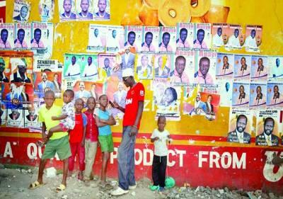 نیروبی: ایک شخص بچوں کے ہمراہ الیکشن میں حصہ لینے والے مختلف امیدواروں کے پوسٹرز کے پاس کھڑا ہے