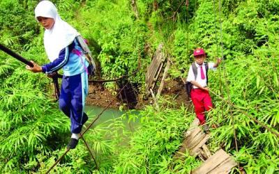 جکارتہ:دو بچے سکول جانے کیلئے رسی کی مدد سے راستہ عبور کر رہے ہیں