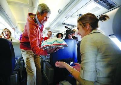 پیرس: امریکی وزیر خارجہ جان کیری جہاز میں دوران سفر صحافی مارگریٹ برینن کو اسکی سالگرہ کے موقع پر کیک پیش کر رہے ہیں
