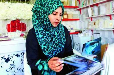 دبئی: ایک عربی خاتون شادی کے لئے لباس خریدنے کیلئے کتاب میں نمونے دیکھ رہی ہے