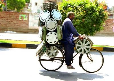 سخت گرمی میں بچوں کا پیٹ پالنے کے لئے ایک محنت کش سائیکل سوار اپنی سائیکل پر گاڑیوں کے ویل لٹکائے ہوئے جارہا ہے(فوٹو ندیم احمد)