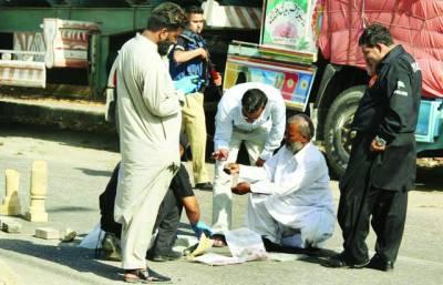 کراچی، بم ڈسپوزل سکواڈ کے اہلکار فٹ پاتھ پر نصب کئے گئے بم کی جگہ سے شواہد اکٹھے کررہے ہیں