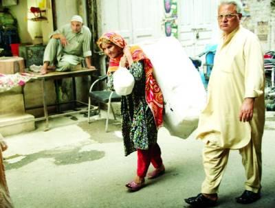اے عمر رفتہ زراٹھہر جا،ایک بزرگ خاتون شدید گرمی میں وزنی بوری اٹھائے جا رہی ہے(ِفوٹو عمر شریف)