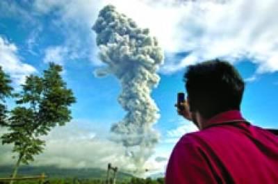 سمراتا: ایک شخص اپنے موبائل فون پر پہاڑ میں سے اٹھتے ہوئے دھویں کو دیکھ رہا ہے