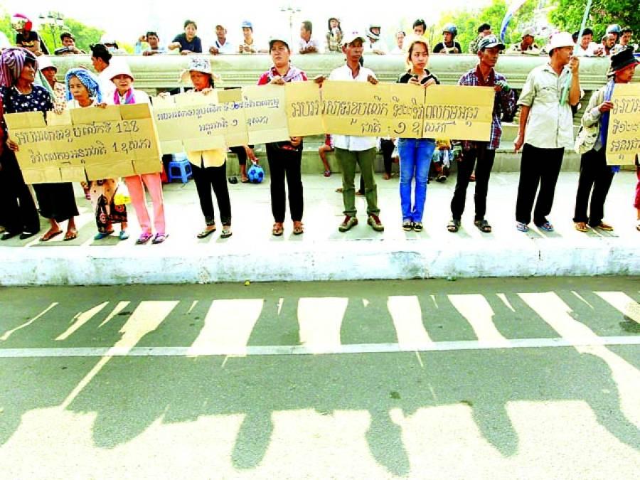 نوم پٹھ:لوگ حکومت کے خلاف احتجاج کے دوران بینرز پکڑے کھڑ ے ہیں