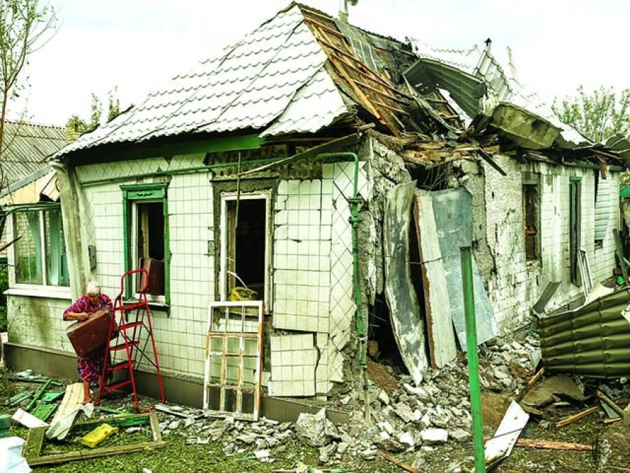 کیف: روسی حامیوں کی بمباری سے تباہ شدہ گھر میں سے خاتون اپنا سامان باہر نکال رہی ہے