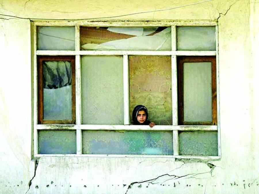 کابل: ایک بچی بم دھماکے سے متاثرہ گھر کی کھڑکی سے باہر دیکھ رہی ہے