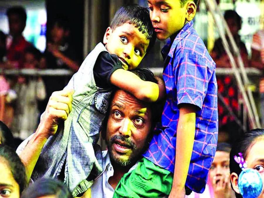 الہ آباد: ایک شخص بچوں کو کندھوں پر اٹھائے مقامی تہوار میں شریک ہے