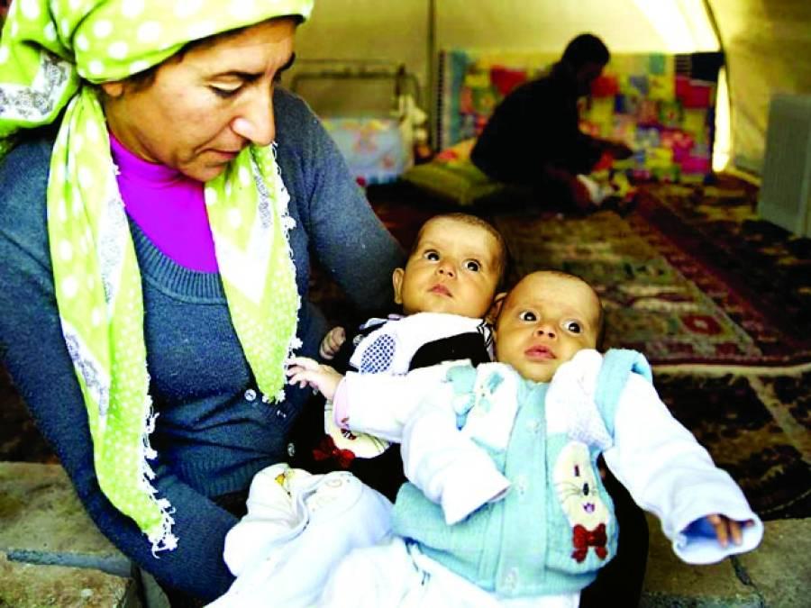 دمشق: پناہ گزیں کیمپ میں ایک خاتون اپنے جڑواں بچوں کو اٹھائے ہوئے ہے