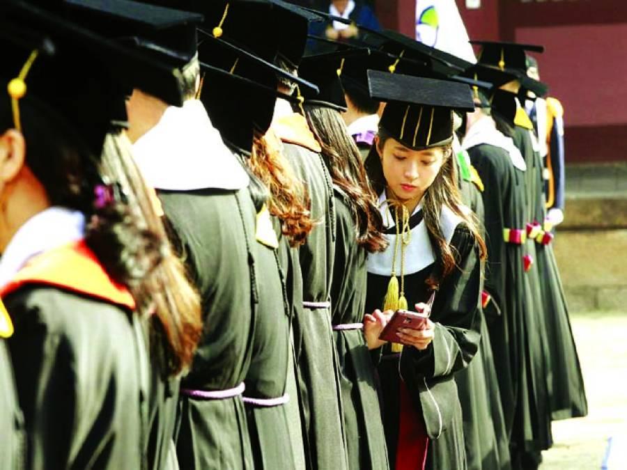 سیول: جنوبی کورین طالبہ گریجویٹ تقریب کے دوران اپنا موبائل فون دیکھ رہی ہے