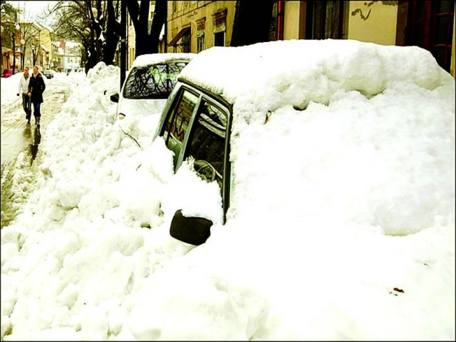 بیجنگ: ایک خاتون برف سے ڈھکی ہوئی کار کی تصویر بنا رہی ہے