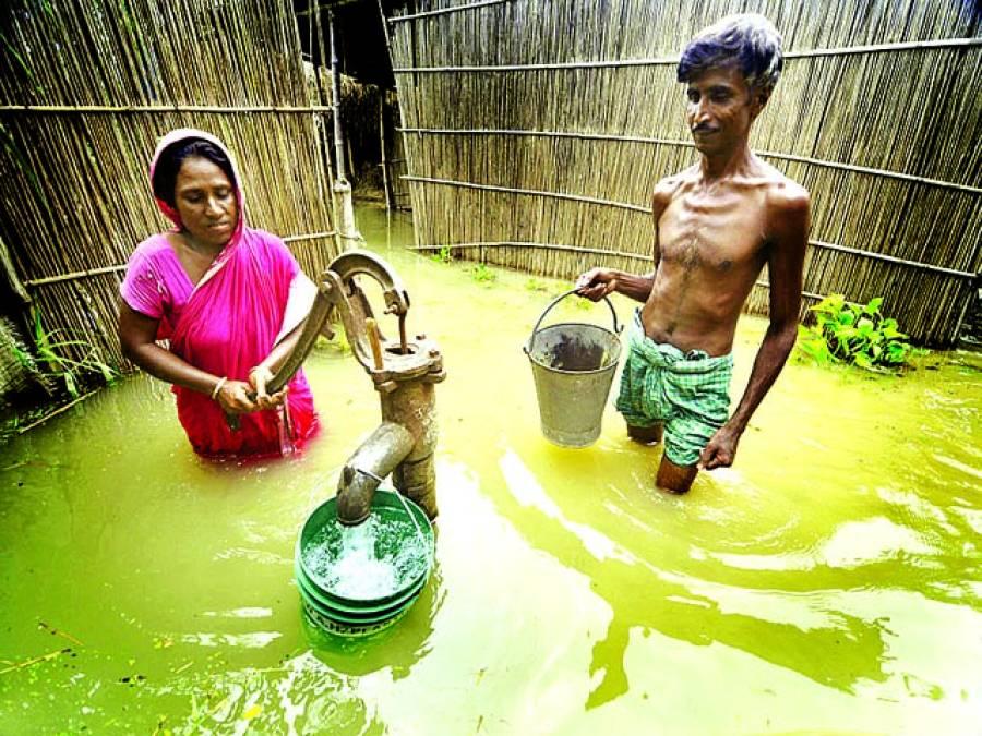 آسام: میاں بیوی سیلابی پانی میں پمپ سے پانی بھر رہے ہیں