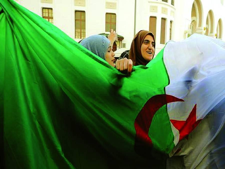 الجزائر میں صدر عبدالعزیز بوتفلیقہ کے خلاف احتجاج کے دوران دو خواتین پرچم اٹھائے ہوئے ہیں۔