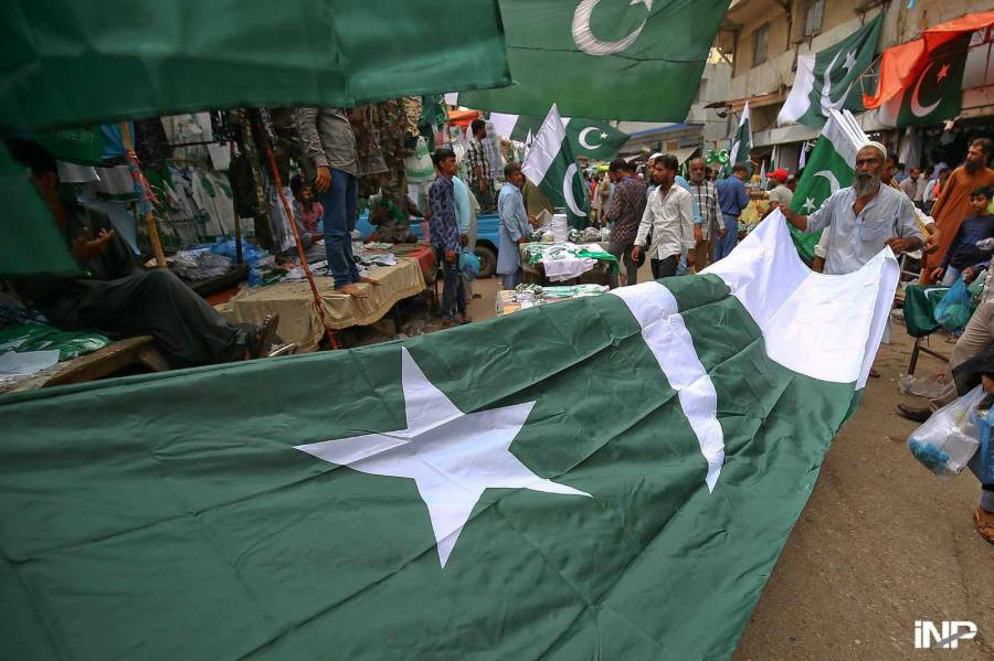 جشن آزادی، ایک دکاندار پاکستان کا قومی پرچم گاہکوں کو دکھا رہا ہے
