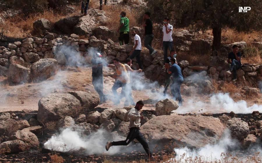 فلسطین، مغربی کنارہ، تصادم، مغربی کنارے کے شہر نابلس کے مشرق میں واقع گائوں بیت دجن میں یہودی آباد کاری میں توسیع کے خلاف مظاہرے کے دوران اسرائیلی فوجیوں سے تصادم پر فلسطینی مظاہرین محفوظ جگہ کی تلاش کے لیے بھاگ رہے ہیں (شنہوا)