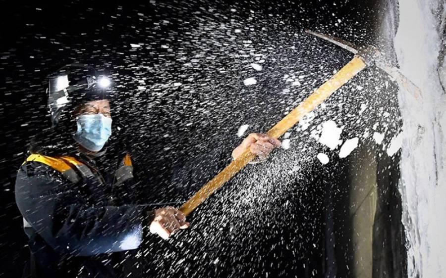 چین کے وسطی صوبے ہینان کے لویانگ میں گوان ان تانگ سرنگ کی دیوار سے گوزین ژونگ جمی ہوئی برف کو صاف کر رہا ہے (شنہوا)