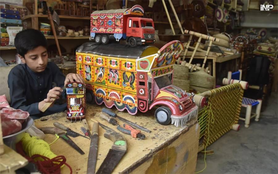 پشاور میں ایک بچہ دکان پر ڈیکوریشن پیش بنا رہا ہے