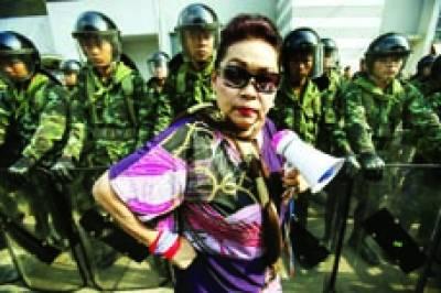 بینکاک: حکومت کے خلاف احتجاج میں ایک عورت شریک ہونے کیلئے جا رہی ہے جبکہ عقب میں سکیورٹی اہلکار ڈیوٹی پر موجود ہیں