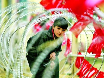 سری نگر: بھارتی پولیس کی جانب سے لگائی گئی خاردار تاروں میں سے کشمیری بچہ گزر رہا ہے