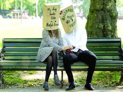 پیرس: ایک جوڑا پیپر بیگ پہنے باغ میں بیٹھا ہو اہے