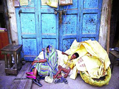 ڈھاکہ: ایک ماں اپنے بچے کے ہمراہ گرمی سے بچاﺅ کیلئے عمارت کے بند درواز ے کے سامنے سو رہی ہے