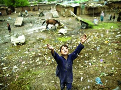کابل: ایک افغانی بچہ امدادگرائے جانے والے ہیلی کاپٹرکی طرف ہاتھ پھیلائے ہوئے ہے