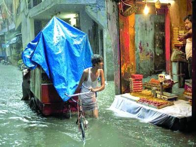 نئی دہلی: ایک شخص مٹھائی کی دکان کے سامنے سے بارش کے پانی میں اپنا چھکڑا لےکر جا رہا ہے