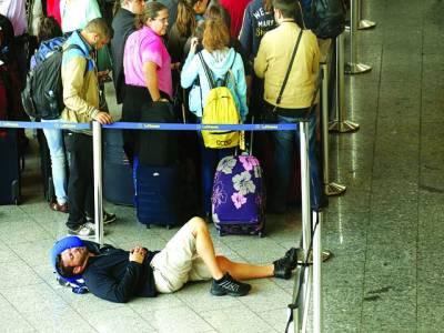 فرینکفرٹ: لفتھانزہ ائر ویز کے ملازمین کی ہڑتال کے باعث ایک شخص فرش پر سویا ہو اہے