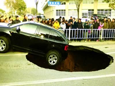 بیجنگ: لوگ گڑھے میں گری ہوئی کار کونکلتے ہوئے دیکھ رہے ہیں