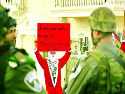 غزہ: فلسطینی شخص سانتا کلاز کا لباس پہنے اسرائیلی فوجیوں کے سامنے مظاہرہ کر رہا ہے